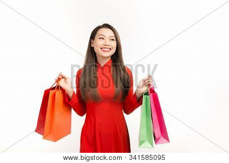 Vietnamese Woman Wearing Traditional Ao Dai Clothes And Holding Shopping Bags In Lunar New Year Fest