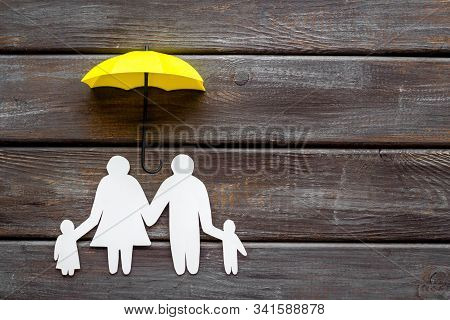 Health Insurance Concept. Family Cutout Under Umbrella On Dark Wooden Background Top-down Copy Space
