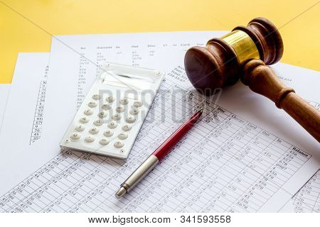 Taxes Debt Concept. Judge Hammer Near Financial Documents On Yellow Background