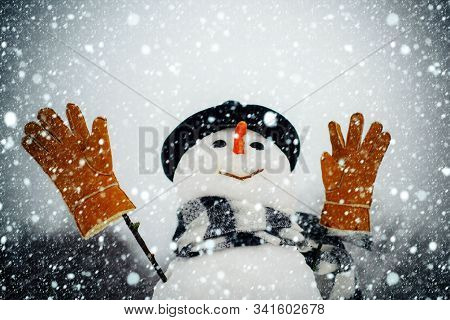 Snowman In A Scarf And Hat. Snowman Wish You Merry Christmas And Happy Holidays. Snowman In Snow For