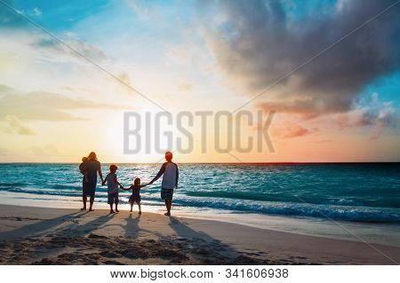 Happy Family With Tree Kids Walk At Sunset Beach