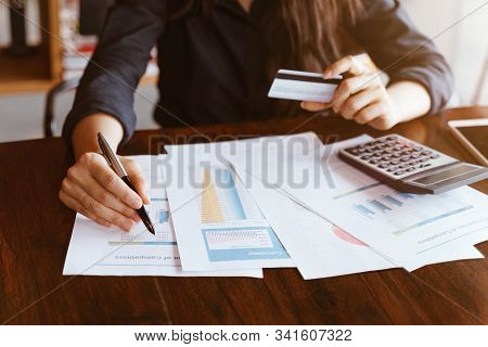 Businesswoman Holding Pen Pointing On Summary Report While Holding Credit Card With Smartphone.techn