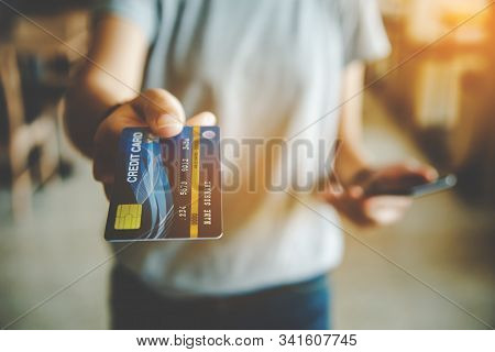 Close Up Of Hand Using Credit Card To Pay By Sending The Credit Card