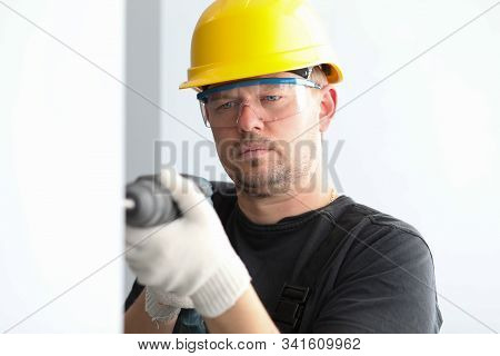 Close-up View Of Concentrated Male Drilling Hole In Wall. Professional Builder Wearing Yellow Protec