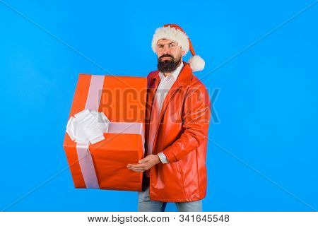 Serious Man With Christmas Present Box. Man With Big Gift Box. Santa Christmas Man Holds Gift Presen