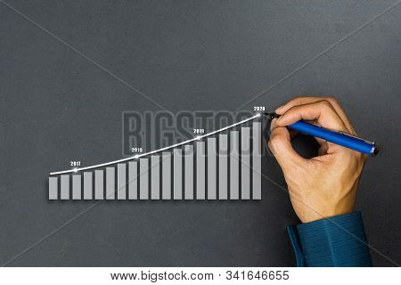 Businessman Drawing Graphics Line Year Growing Graph. Describe The Organization's Management Plan Or