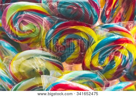 Group Of Vivid Colored Lollipops In Display For Sale At A Candy Store In Individual Plastic Packagin