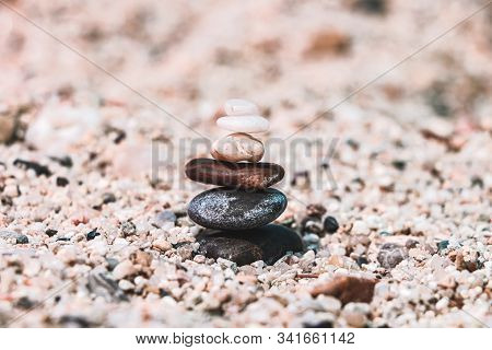 Selective Focus On The Turret Of Stones In The Sand On A Blurred Background. The Concept Of Equilibr
