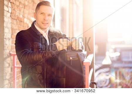 Young man with bag on walk in city against backdrop of modern buildings at day.