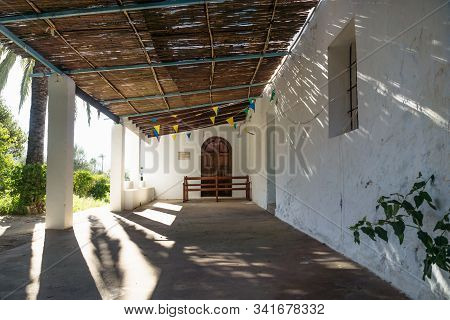 Entrance With Palm Tree Of Abadoned Church Ermita De Sant Antoni Y Sant Jaume In Cap Blanche With Dr