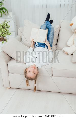 Funny Little Kid Is Lying On The Sofa Upside Down, Showing Tongue, Legs On The Back Of The Sofa, Pla