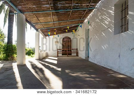 Entrance Of Abadoned Church Ermita De Sant Antoni Y Sant Jaume In Cap Blanche With Dramatic Sun Rays