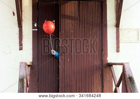 Childrens Hand In A Blue Jacket Protruding From Behind A Door With A Red Ball