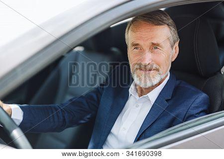 Senior Driver Sitting Inside A Car Wearing Formal Wear