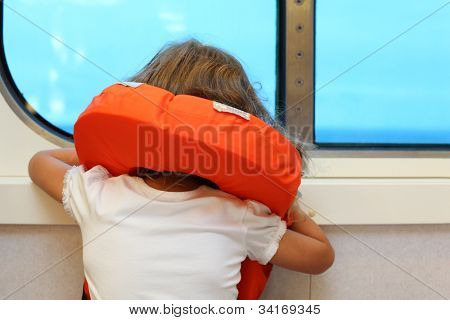 Back of little girl dressed in life jacket, which stands near window in cabin of ship and looks into distance