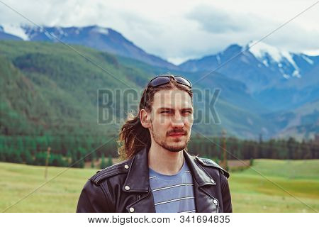 The Guy Stands Against The Background Of Snowy Mountains With Snow-capped Peaks