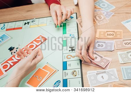 Kyiv, Ukraine - November 15, 2019: Cropped View Of Women Playing Monopoly Game At Table
