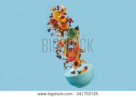 Dried And Candied Fruits And Nuts Flying Above Blue Ceramic Bowl On Blue Background. Stock Photo Of