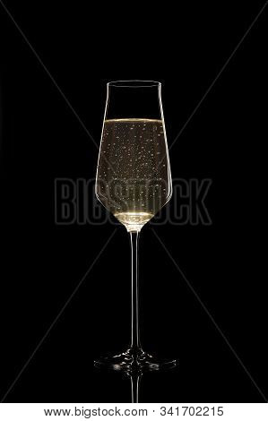 An Unusual Thin Filled Champagne Glass With Bubbles Isolated On Black Background. Stock Photo Of Lux
