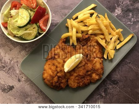 Wiener Schnitzel With French Fries, Salad And Lemon.