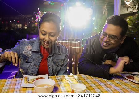 A Jovial Young Smiling Couple Dressed In Casual Attire In Happy Mood Having Food On A Dinner Table.