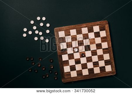 Top View Of Checkerboard With Checkers Isolated On Black