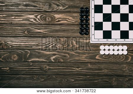 Top View Of Checkers Beside Checkerboard On Wooden Background With Copy Space