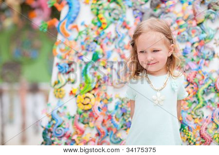 Little girl at crafts market with traditional souvenirs of Turks and Caicos