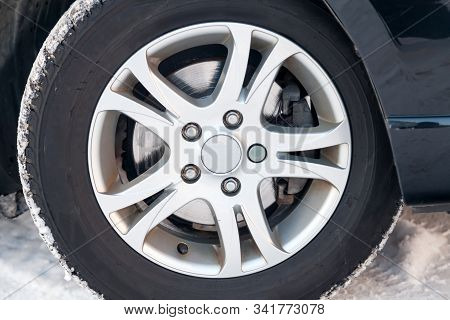 An Aluminum Alloy Wheel With Winter Studded Tires On A Black Car With A Poorly Worn Brake Disk Requi