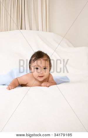 Ethnic Baby Boy Lying Down On Blanket