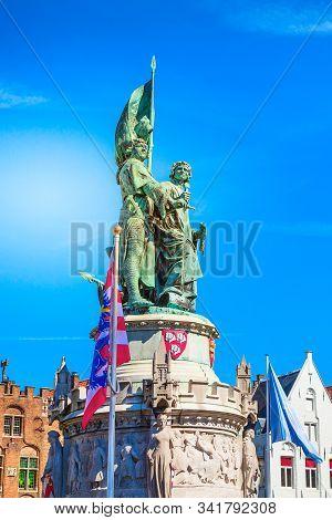 Bruges, Belgium Statue Of Jan Breydel And Pieter De Coninck And The Flag Of Brugge At The Market Squ