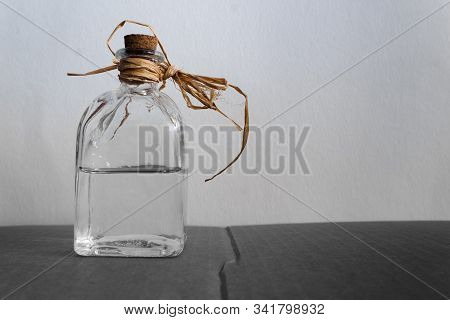 Tied & Corked, Half Empty Bottle Of Transparent Spirits.