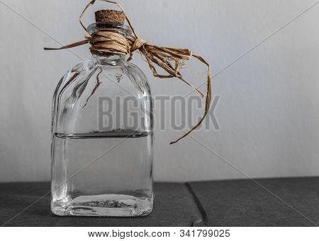 Tied & Corked, Half-empty Bottle Of Transparent Spirits.