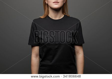 Cropped View Of Woman In Blank Basic Black T-shirt On Black Background