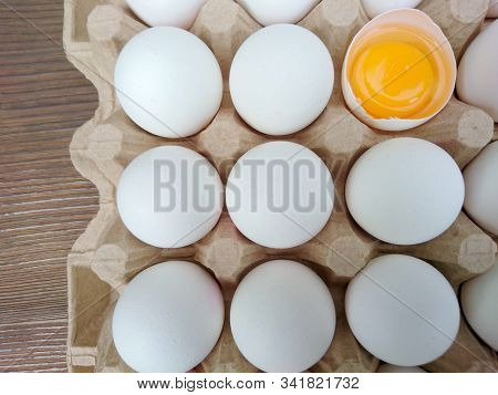 White Eggs Carton & Cracked Egg Half With Yolk Top View On Wooden Background. Broken And Whole Eggs