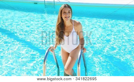 Happy Beautiful Girl With White Swimsuit Coming Out From Swimming Pool Water. Pretty Healthy Young W