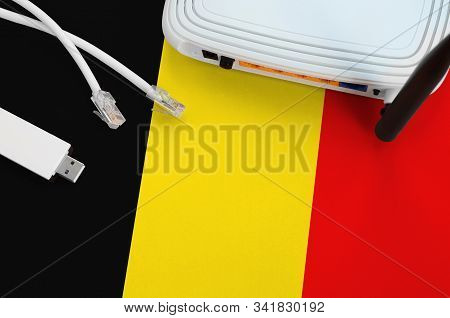 Belgium Flag Depicted On Table With Internet Rj45 Cable, Wireless Usb Wifi Adapter And Router. Inter