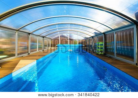 Swimming Pool With Blue Water And Transparent Plastic Tent. Modern Pool Design With Collapsible Wall