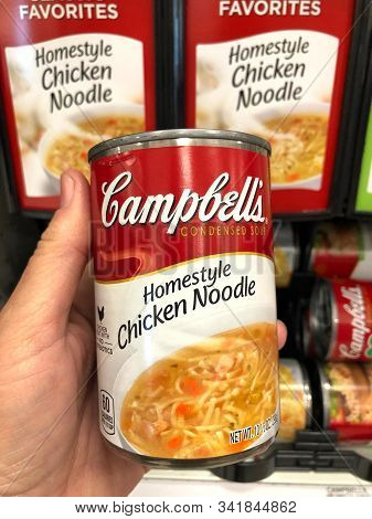 Alameda, Ca - Nov 19, 2019: Hand Holding Can Of Campbells Brand Condensed Chicken Noodle Soup In Fro