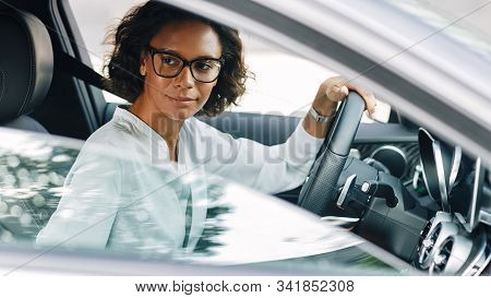 Young Female Entrepreneur Driving A Car Looking Away