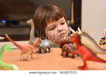 Child Play With A Dinosaur Toys. Boy Having Fun Playing With A Toy Dinosaur, Little Paleontologist