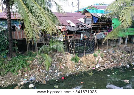 RANONG, THAILAND - 26 DECEMBER 2019: Poverty and pollution. Rohingya refugees from Myanmar live in poor slum beside river polluted with plastic and sewage.