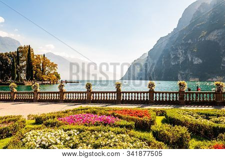 Garda Lake Promenade With Colorful Flowerbeds With Growing And Blooming Plants, Classic Stone Fence