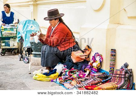 Cusco , Peru- Jan 9, 2019: Quechua woman with her caring bag in main street of  Cusco City, Peru.