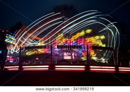 READING, UK - DECEMBER 27, 2019: Bright light trails from a moving jump and smile thrill ride at a Christmas funfair in Reading, Berkshire, UK.