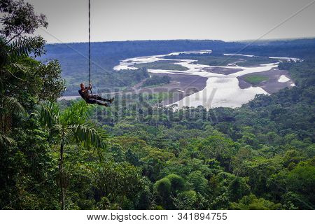 Tourist Having Fun In The Air Held By A Rope. Fabulous Amazonian Landscape Where You Can Appreciate