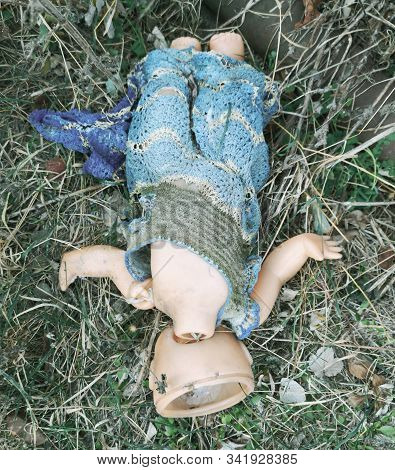 An Old Headless Doll Lies On The Ground.