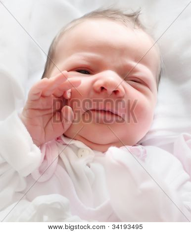 Funny portrait of a newborn baby girl - first salute.
