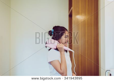 Happy Asian Woman Using Electric Curling Iron With Hair In Bedroom,straightening Hair,straightener