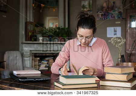 Exam Preparation. Attractive Brunette Student Girl In Glasses And A Pink Sweater Leaned Over Books,